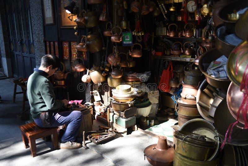 Un calderero está construyendo un bronce delante de su propia tienda del calderero fotografía de archivo libre de regalías