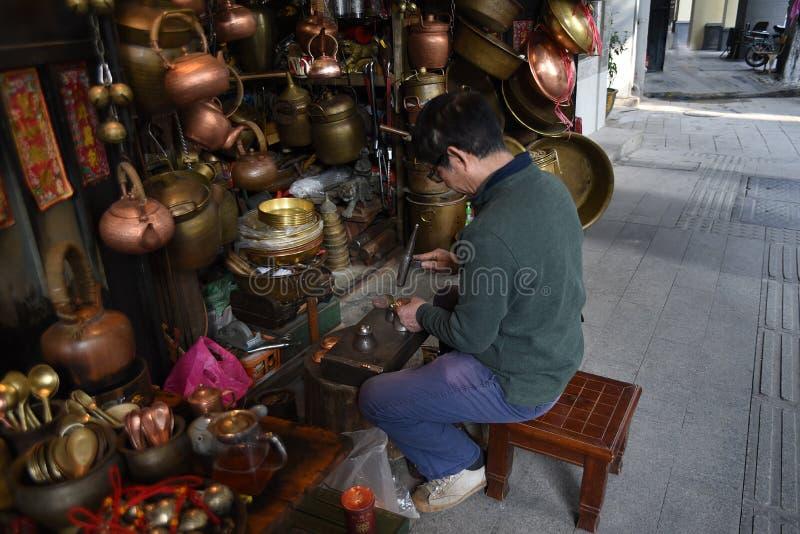 Un calderero está construyendo un bronce delante de su propia tienda del calderero imágenes de archivo libres de regalías