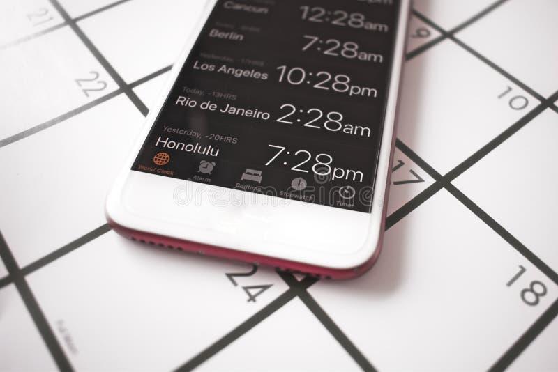 Un calendario y una hora mundial app en un teléfono móvil se utilizan para el viaje que planea a las zonas de momento diferente imagen de archivo libre de regalías