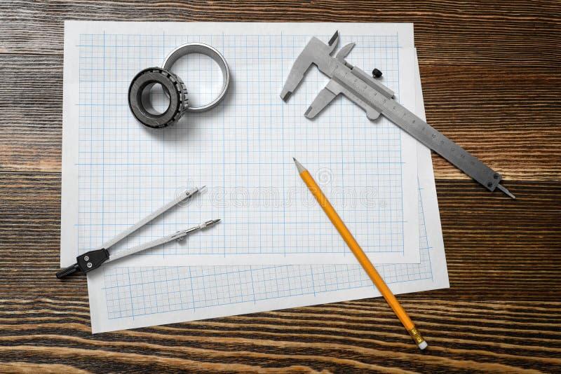 Un calibrador a vernier que lleva a cabo un transporte, un lápiz y un par de compases que mienten sobre el proyecto en el fondo d foto de archivo libre de regalías
