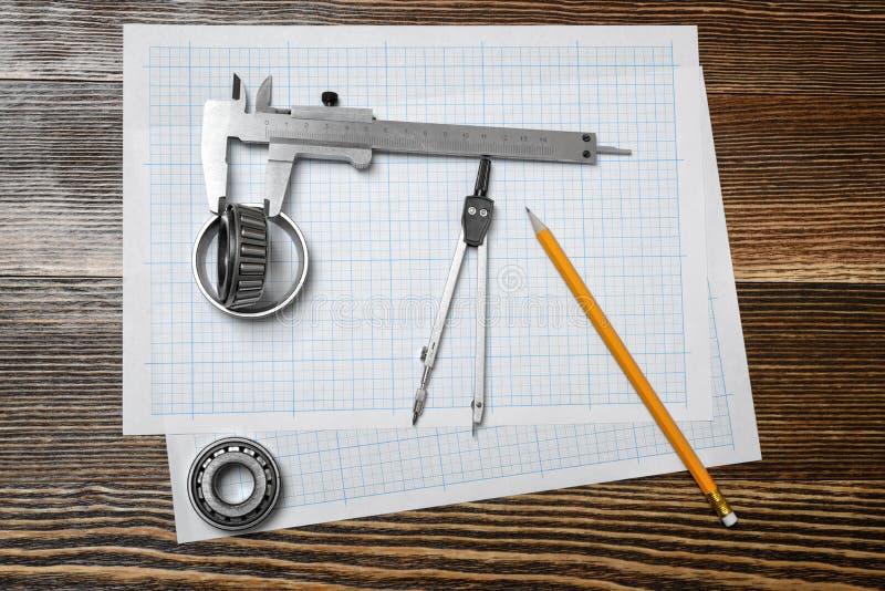 Un calibrador a vernier que lleva a cabo un transporte, un lápiz y un par de compases que mienten sobre el proyecto en el fondo d imagen de archivo libre de regalías