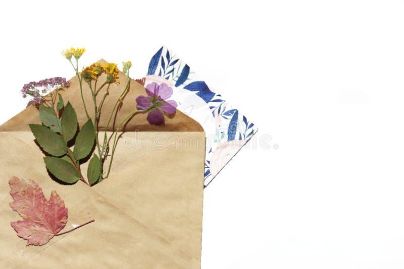 Un calibre avec l'enveloppe, la carte postale et les fleurs photographie stock libre de droits