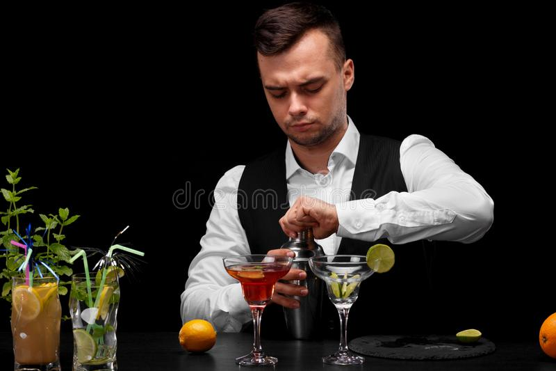 Un camarero abre una coctelera, un contador con los vidrios del margarita, limón, cal, cócteles de la barra en un fondo negro foto de archivo