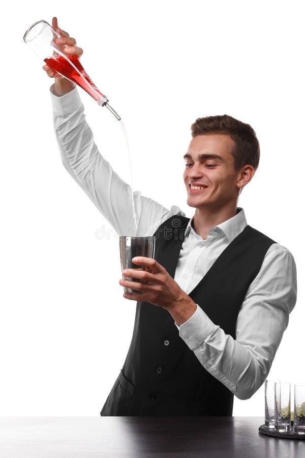Un camarero atractivo en un contador de la barra que hace un cóctel, una placa de la cal aislada en un fondo blanco fotografía de archivo libre de regalías