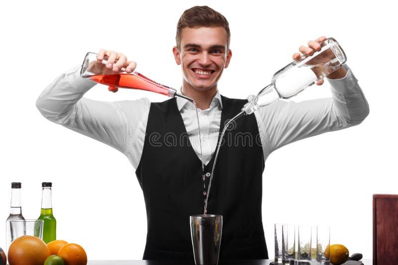 Un camarero atractivo en un contador de la barra que hace un cóctel, una placa de la cal aislada en un fondo blanco imágenes de archivo libres de regalías