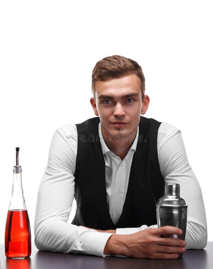 Un camarero atractivo en el contador de la barra, una coctelera del metal, una botella de whisky en un fondo blanco imagenes de archivo