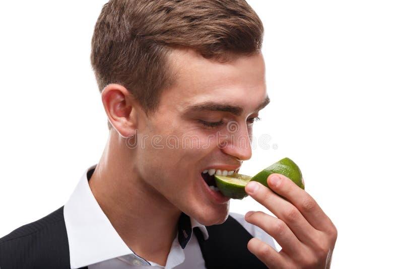 Un camarero atractivo muerde una cal verde jugosa, cócteles en un club de noche en el fondo blanco fotos de archivo