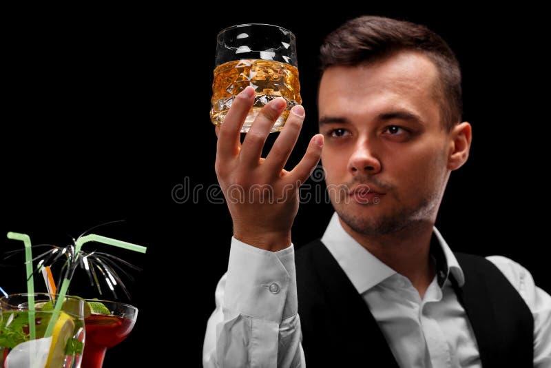 Un camarero atractivo sostiene un vidrio del whisky, vidrios del margarita en un contador de la barra en un fondo negro imágenes de archivo libres de regalías