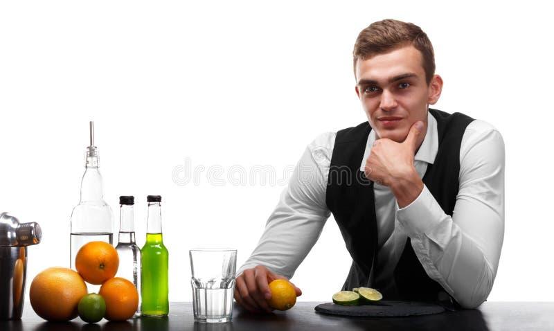 Un camarero detrás de un contador de la barra con los ingredientes para los cócteles, aislados en un fondo blanco Servicio del re foto de archivo libre de regalías
