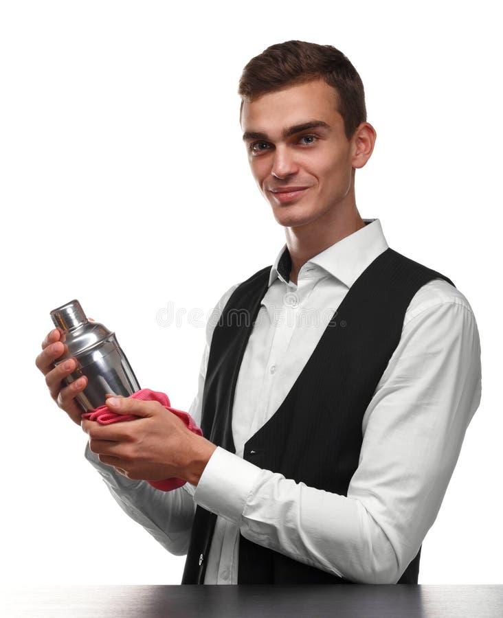 Un camarero en el contador de la barra limpia una coctelera con un trapo rosado aislado en un fondo blanco imagen de archivo