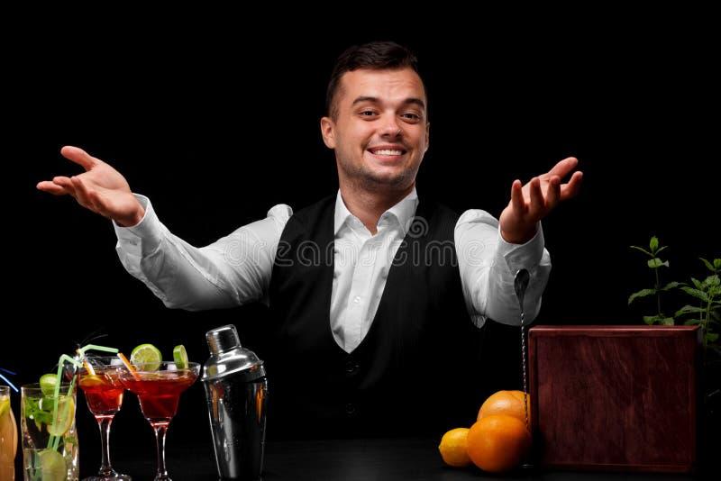 Un camarero feliz en un traje clásico en un fondo negro Muchos ingredientes coloridos para los cócteles en una tabla imágenes de archivo libres de regalías