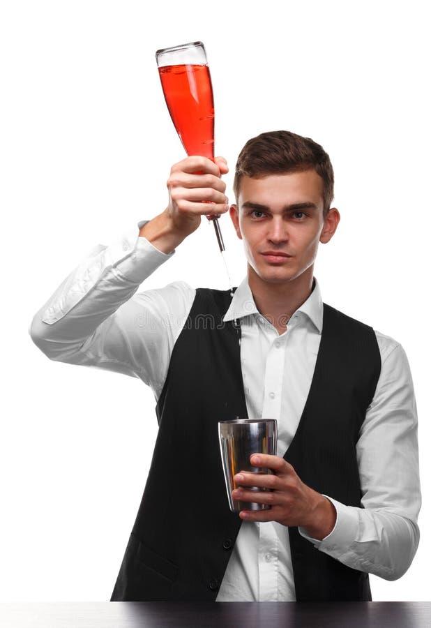 Un camarero hermoso en un contador de la barra vierte el whisky en una coctelera del metal aislada en un fondo blanco fotografía de archivo