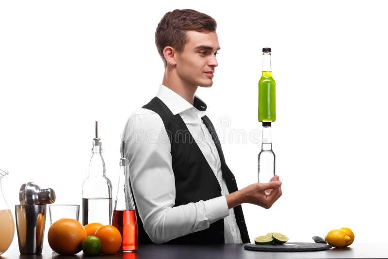 Un camarero hermoso sostiene las botellas con las bebidas, un contador de la barra con la cal, limón aislado en un fondo blanco foto de archivo