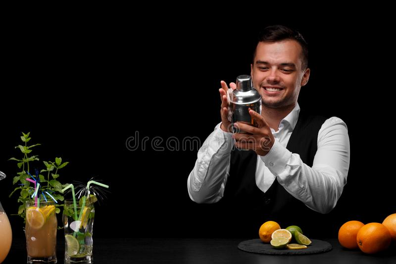 Un camarero limpia una coctelera en el contador de la barra, limón, cal, naranjas, cócteles en un fondo negro fotos de archivo