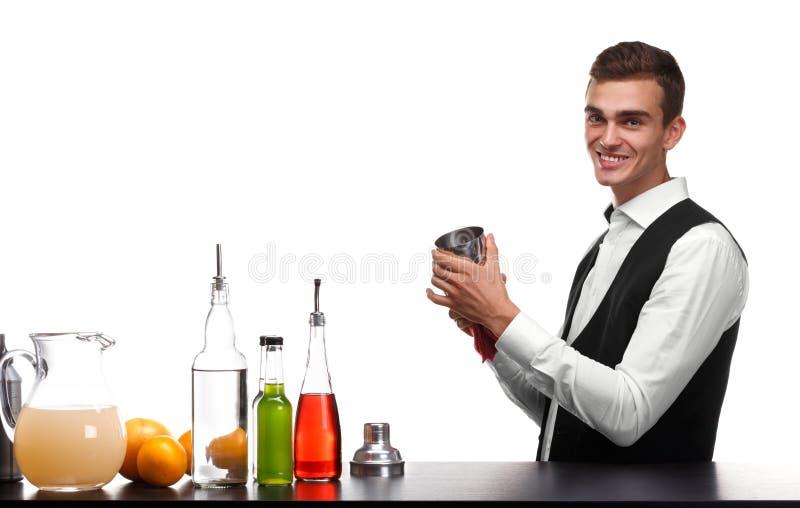 Un camarero que limpia una coctelera para las bebidas, aislada en un fondo blanco Ingredientes del cóctel en un contador de la ba imagenes de archivo