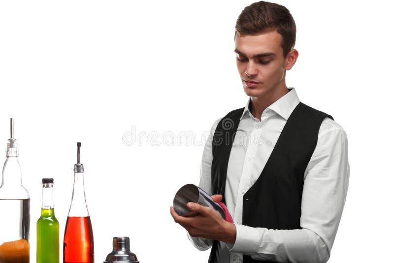 Un camarero que limpia una coctelera para las bebidas, aislada en un fondo blanco Ingredientes del cóctel en un contador de la ba imagen de archivo libre de regalías