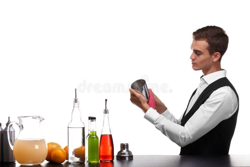 Un camarero que limpia una coctelera para las bebidas, aislada en un fondo blanco Ingredientes del cóctel en un contador de la ba foto de archivo