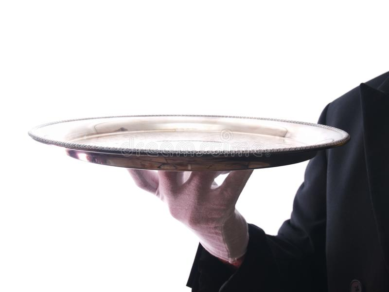 Un camarero que sostiene una bandeja de plata fotografía de archivo libre de regalías