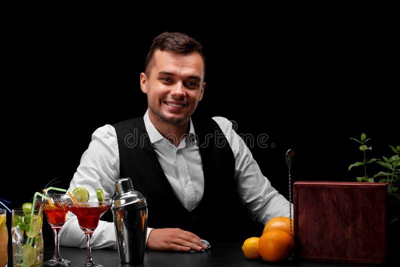 Un camarero sonriente limpia la tabla con un trapo azul en un fondo negro Servicio del restaurante y concepto del entretenimiento fotos de archivo