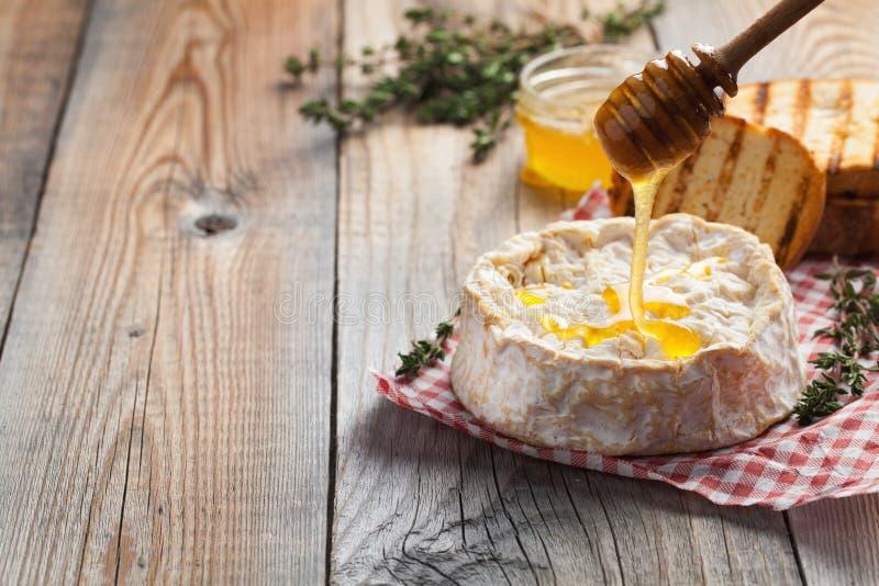 Un camembert real de Francia con tomillo, miel y pan tostado en la tabla rústica de madera vieja Queso suave en los wi de madera  imagen de archivo libre de regalías