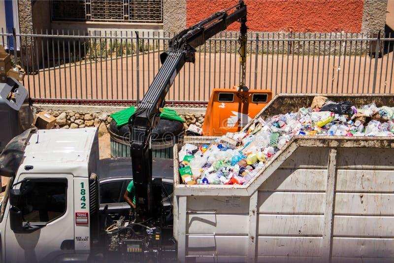 Un camión de basura levanta los tanques con una grúa y los vierte en el cuerpo fotos de archivo libres de regalías