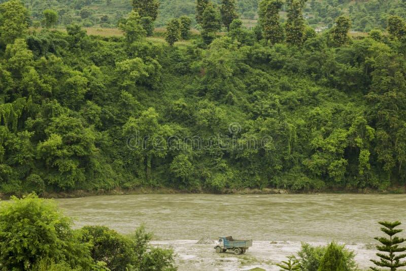 Un camión grande se coloca en el banco de un río rápido de la montaña en medio de los altos bancos verdes demasiado grandes para  fotos de archivo