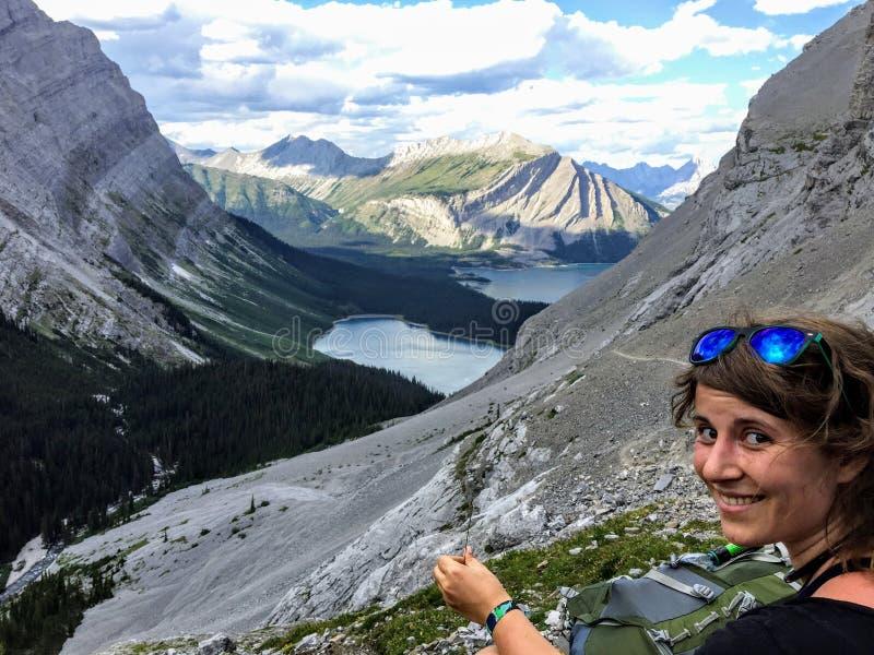 Un caminante de la mujer joven que admira la visión desde el lado de la montaña Abajo abajo está las montañas rocosas y el lago s foto de archivo