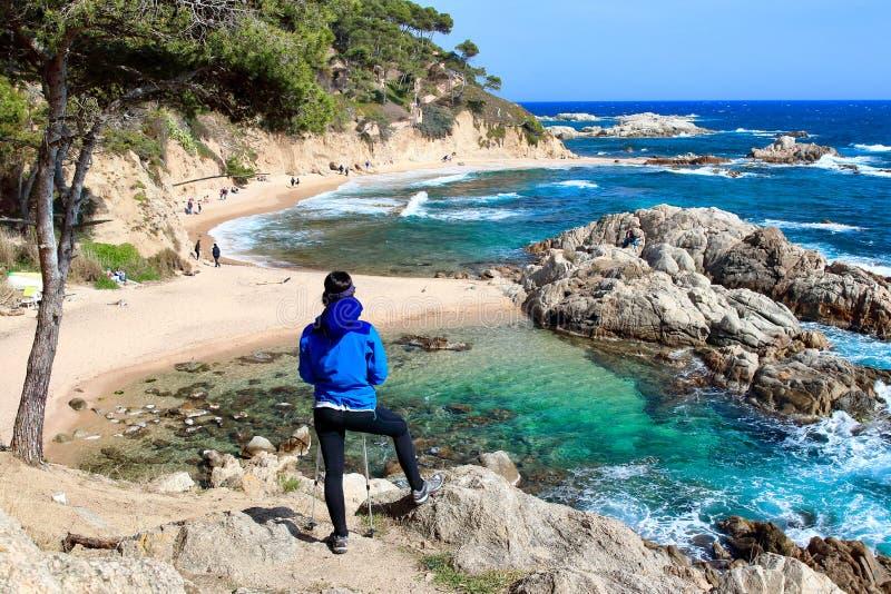 Un caminante femenino joven que mira un paisaje asombroso en la playa de 'Cala Estreta ', la Costa Brava, Cataluña, Spaon imagen de archivo