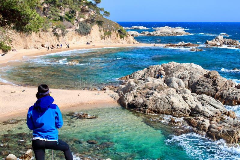 Un caminante femenino joven que mira un paisaje asombroso en la playa de 'Cala Estreta ', la Costa Brava, Cataluña, Spaon fotografía de archivo