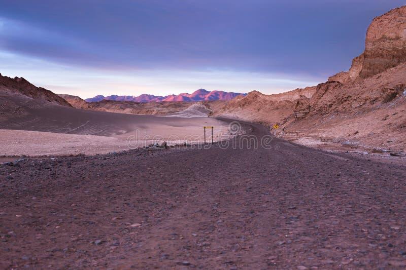 Un camino de tierra lleva a las montañas hermosas distantes del desierto de atacama imagen de archivo