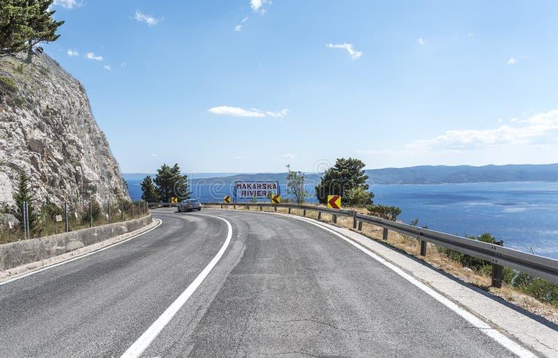 Un camino del automóvil a lo largo de la costa de mar del centro turístico de Makarska Riviera en Croacia imagenes de archivo