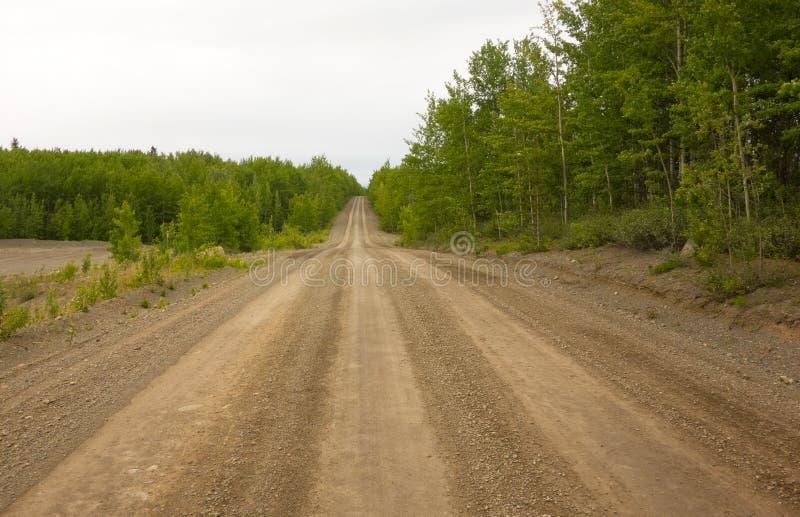 Un camino desafiador que lleva a un destino remoto en Canadá septentrional imagen de archivo