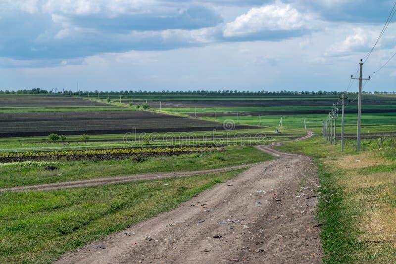 Un camino rural con los pilares de la electricidad en el borde fotos de archivo