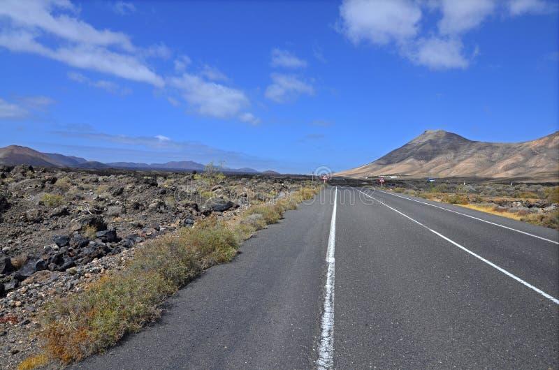 Un camino vacío con el paisaje volcánico de Lanzarote imagen de archivo