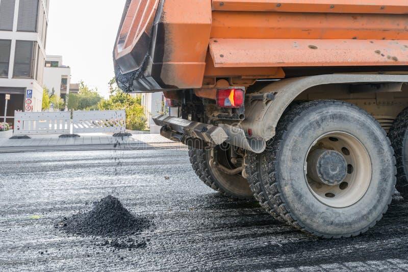 Un camion à benne basculante apporte l'asphalte chaud pour le renouvellement d'un revêtement de la chaussée, Allemagne photographie stock libre de droits