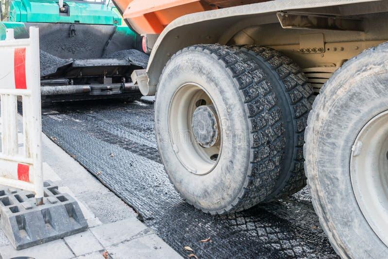 Un camion à benne basculante apporte l'asphalte chaud pour le renouvellement d'un revêtement de la chaussée, Allemagne images libres de droits