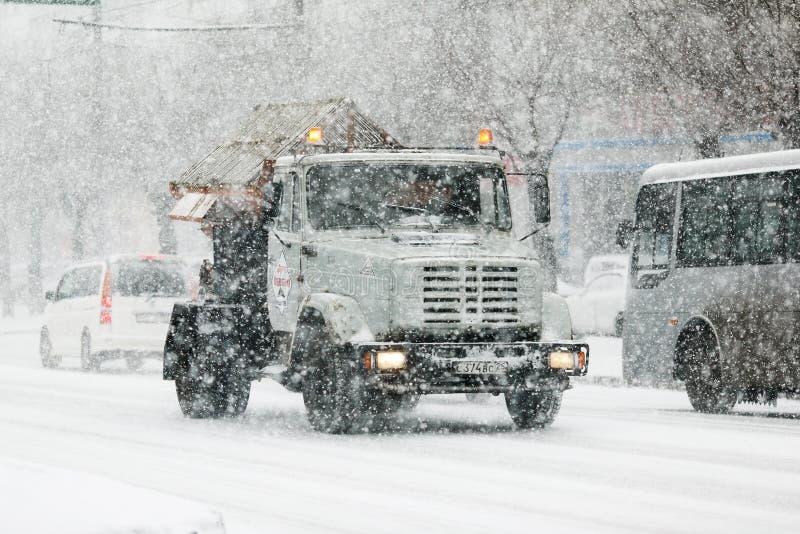 Un camion de service des commandes de ville sur des routes urbaines et des réactifs de dispersions pendant un Sn photo libre de droits
