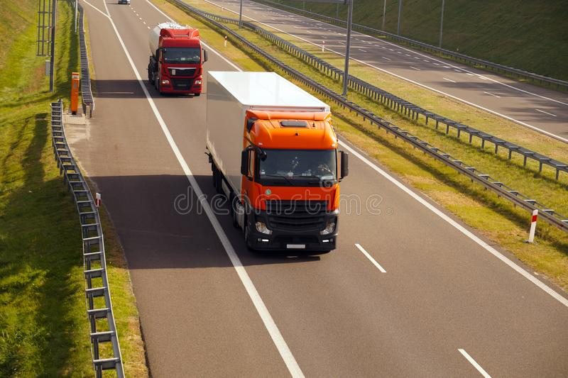 Un camion rosso con un semirimorchio e un'autocisterna che guidano su una strada rapida fotografia stock libera da diritti