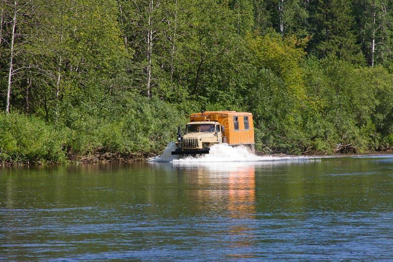 Un camion si muove per scolarsi il fiume immagini stock