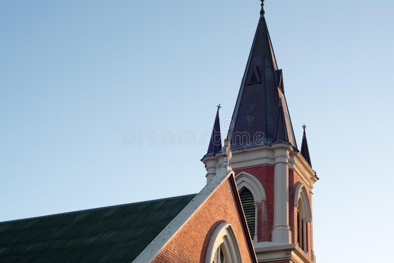 Un campanile della chiesa contro un chiaro cielo blu al tramonto fotografie stock libere da diritti