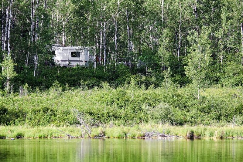 Un campeggiatore nascosto negli alberi accanto ad acqua fotografia stock