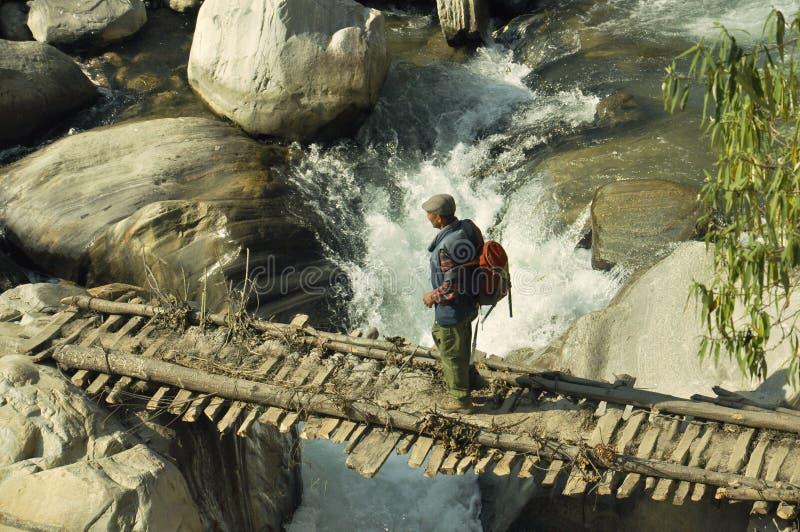 Un campesino está caminando a lo largo del puente sobre el río fotos de archivo libres de regalías
