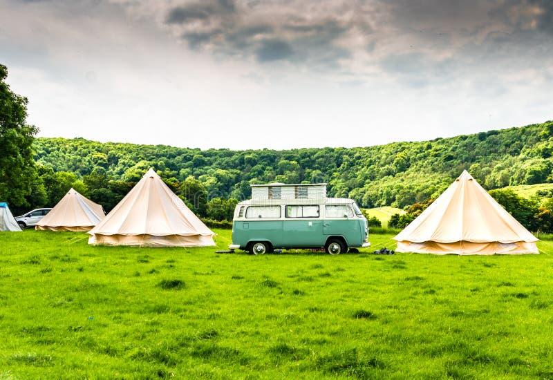 Un campeur iconique ou Kombi de VW à un site glamping dans la campagne anglaise photographie stock libre de droits