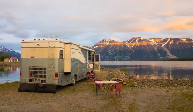 Un camping-car avec une vue renversante d'un lac immobile dans le Canada du nord image libre de droits