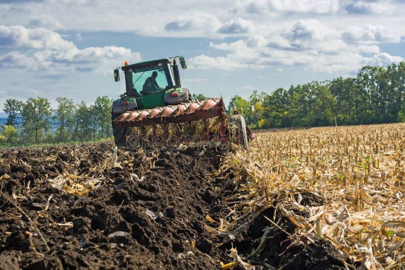 Un campo arato dopo la raccolta del cereale con un trattore completo con un aratro del otto-corpo contro il cielo ed il paesaggio immagine stock