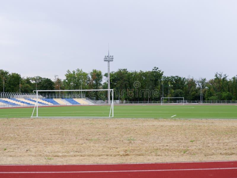Un campo de fútbol verde claro en un fondo natural Un campo de fútbol moderno con las puertas, los sofitos, y los asientos plásti fotografía de archivo libre de regalías