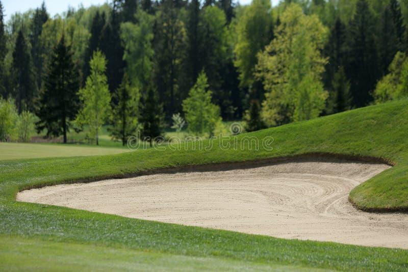 Un campo de golf con los caminos, las arcones y las charcas y con la bandera fotografía de archivo libre de regalías
