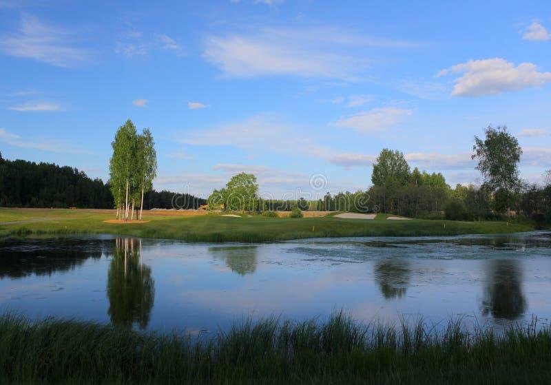 Un campo de golf con los caminos, las arcones y las charcas y con un lago fotos de archivo