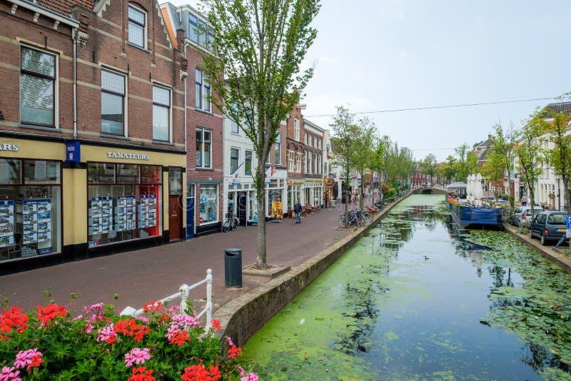 Un canal viejo con un barco de la terraza, porciones de lenteja de agua en el centro foto de archivo
