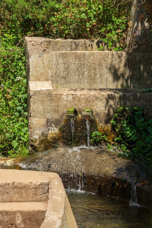 In un canale concreto ha guidato Levada, affluenza dell'acqua attraverso due fori nel calcestruzzo immagine stock